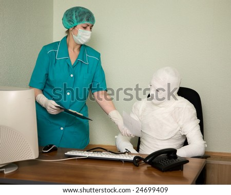 The patient similar to a mummy and the doctor, at office - stock photo