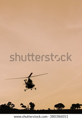 The patrol helicopter flying in the sunset sky