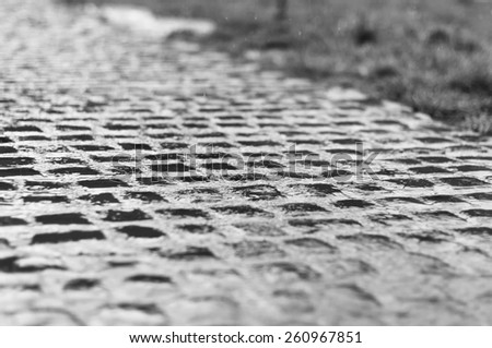 The pattern of stone block paving in the rain - stock photo