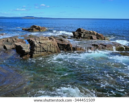 The patterns and beautiful luminous blue-green color of incoming waves and the foam they create as they hit the coastal boulders, add scenic drama to the Maine coastline. - stock photo