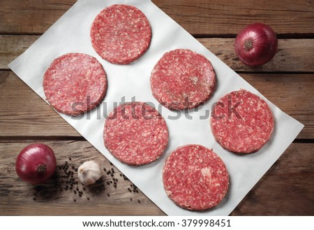the patties of minced meat on white paper - stock photo