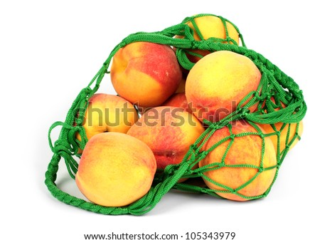 The peaches in a green string bag isolated on white background - stock photo