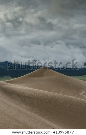 The peak of a sand dune in Great Sand Dunes National Park with low stormy clouds approaching