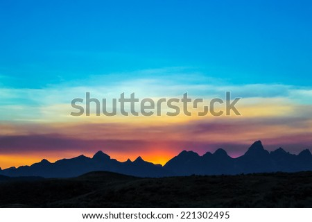 The peaks of the Cathedral Group of the Teton Mountain Range, near Jackson Hole, Wyoming, are silhouetted by a colorful sky at sunset. Grand Teton National Park. - stock photo