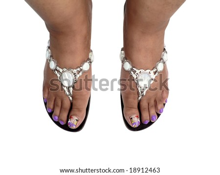 the pedicured feet of an African American woman wearing jeweled sandals isolated on a white background via clipping path - stock photo