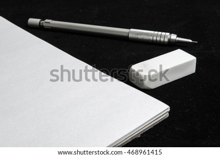 The pencil, eraser and book on black background.