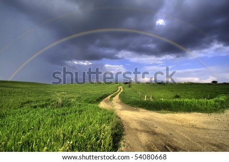 The perfect double rainbow over a beautiful meadow in spring - stock photo