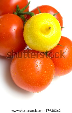 The perfect juicy tomatoes and lemon covered by drops of water, on a green branch. Isolation on white. Shallow DOF.