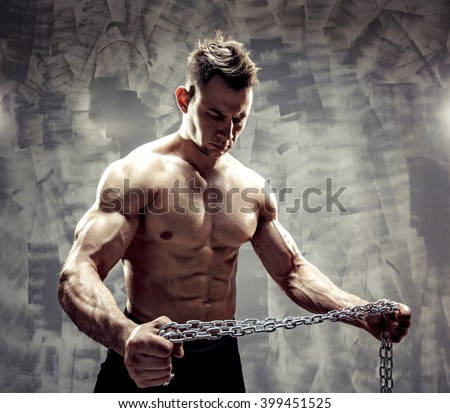The Perfect male body. Awesome bodybuilder. One handsome sexual strong young man with muscular body holding rope with hand hanging on neck and shoulders standing posing in studio. strained biceps. - stock photo