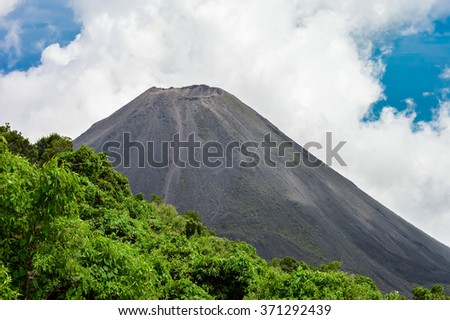 The perfect peak of the active and young Izalco volcano seen from a view point in Cerro Verde National Park in El Salvador. Nearly covered with thick white clouds. - stock photo