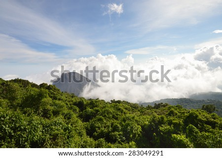 The perfect rocky dusty peak of the active and young Izalco volcano nearly covered by white clouds, seen from one of the view points in Cerro Verde National Park near Santa Ana, El Salvador - stock photo