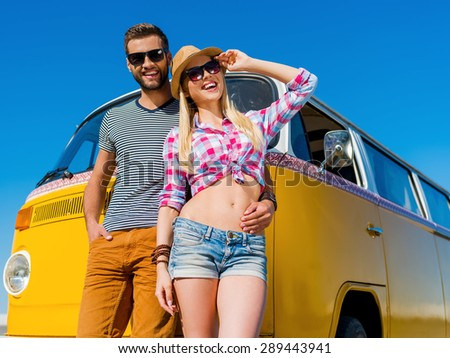 The perfect summer date. Cheerful young man embracing his girlfriend while both leaning at their retro mini van - stock photo