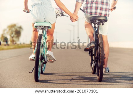 The perfect summer date. Rear view of young couple holding hands while riding on bicycles along the road - stock photo