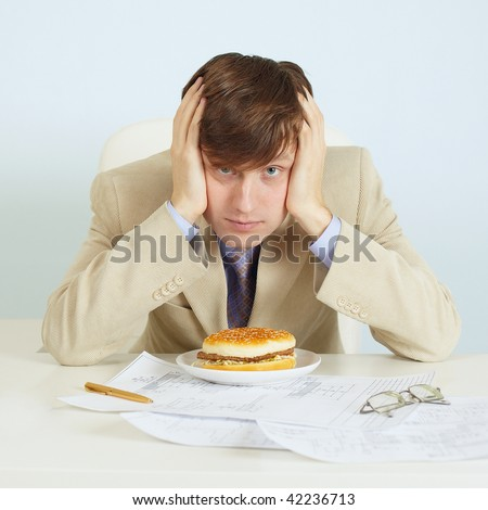 The person at office on a workplace with a hamburger