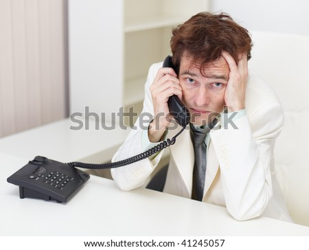 The person excited communicates by phone sitting at a table at office - stock photo