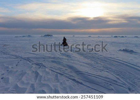 The person going on a snowmobile on the frozen river in the winter at sunset