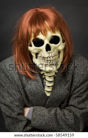 The person in a mask of death from latex and a red wig