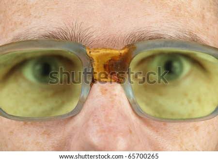 The person in old bad spectacles with a poor eyesight close up - stock photo