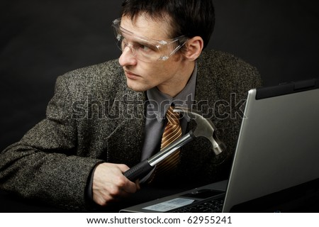 The person is going to break the computer by means of a hammer - stock photo