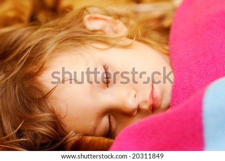The person of the little girl which sleeps on the bed, having taken cover a woolen blanket.