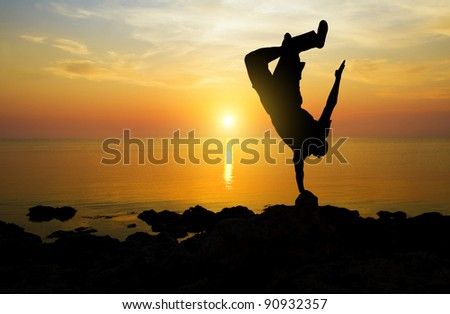 The person on a decline on an ocean coast does a somersault - stock photo