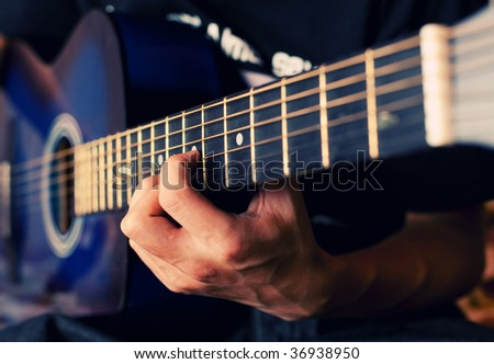 The person plays a guitar, fingers hold a chord - stock photo