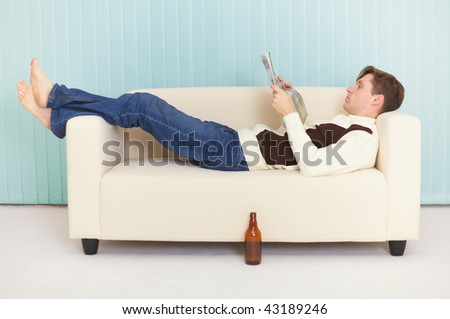 The person reads magazine comfortably lying on a sofa - stock photo