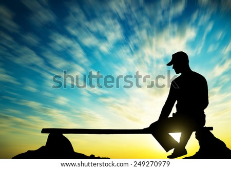 The person sits on a bench against the sky - stock photo