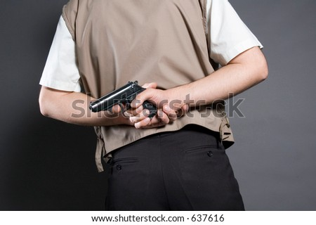 The person with a pistol behind a back - stock photo