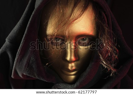 The person with long hair in a gold mask. - stock photo