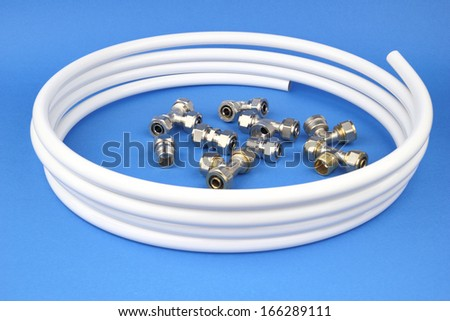 The pex pipe and armature on the blue background - stock photo