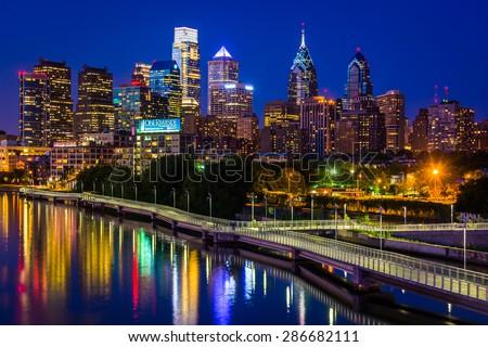 The Philadelphia skyline and Schuylkill River at night, seen from the South Street Bridge in Philadelphia, Pennsylvania. - stock photo