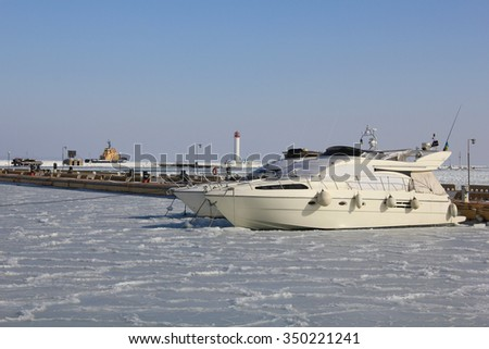 The photo is made in the winter, in the Odessa port. Boats on the winter parking, frozen in ice. The beacon is in the distance visible. Around ice.