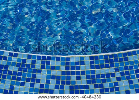 The photo of pool with water covered with blue mosaic