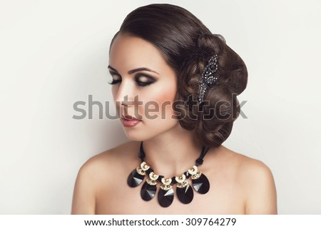 The photo shows a girl with an evening make-up and beautiful hair bulk hair-style, sultry brunette, sexy necked shoulders, dreaming desire. Preparing for prom banquet, date, wedding. Luxury saloon.  - stock photo