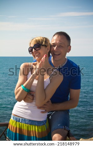 The photo shows a young man and a young woman. They are at the seaside.