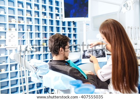 The photo with teeth, Overview of dental caries prevention. man at the dentist's chair during a dental procedure. Doctor shows him a picture of the problems of the teeth.  - stock photo