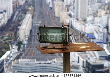 The photograph of a rusty spotlight on a skyscraper with rails in the background / Rusty spotlight