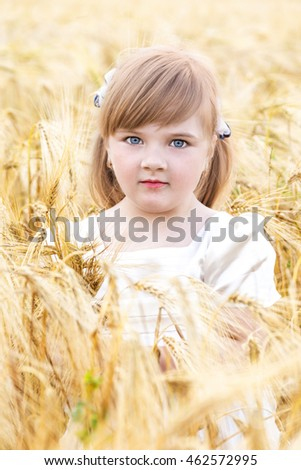 The photograph shows a girl on a wheat field