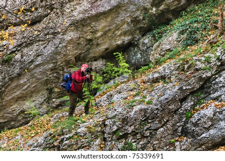 The photographer in a red jacket with camera tripod on a slope of a rock. Autumn leaves. - stock photo