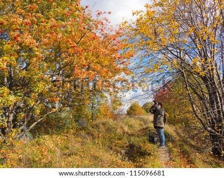 the photographer in the autumn outdoors in a sunny day