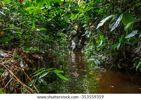 The photographer in the jungle goes through a bog. Republic of Congo. Africa - stock photo