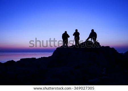 The photographer in the silhouette of the sea - stock photo