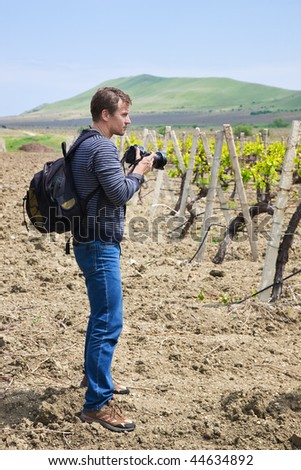 The photographer on a background of mountain is going take pictures of vineyard - stock photo