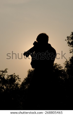 The Photographer' Silhouette:Silhouette of a photographer during a commercial photo-shoot clicking images with his Dslr Camera  - stock photo