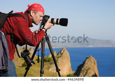 The photographer with the camera on a tripod. On a background the sea and rocks - stock photo
