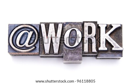 "The phrase ""At Work"" in letterpress type. Cross processed, narrow focus. - stock photo"