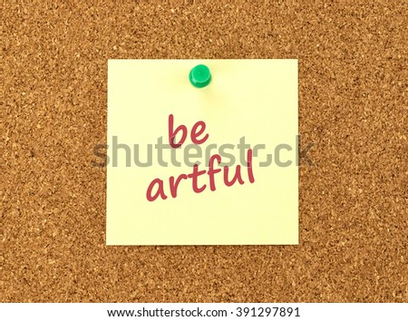 The phrase Be Artful in red text on a yellow sticky note posted to a cork notice board.