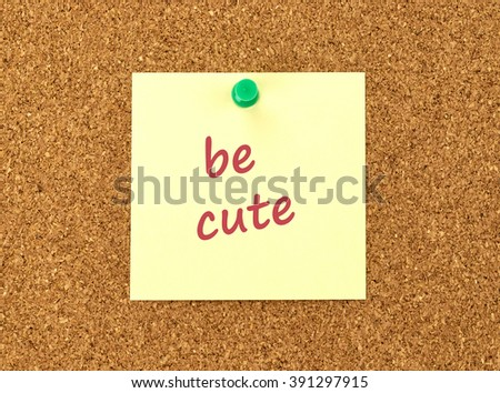 The phrase Be Cute in red text on a yellow sticky note posted to a cork notice board.