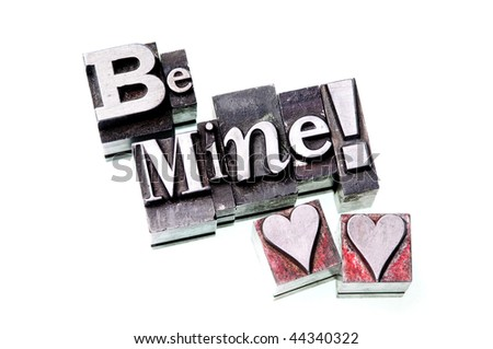"The phrase ""Be Mine!"" in letterpress type with red hearts - stock photo"